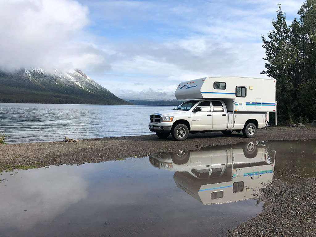 camper truck with reflection in the water - how to choose vehicle for roadtrip